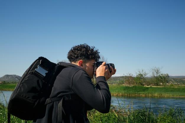 Homme avec sac à dos, prenant une photo de l'eau qui coule