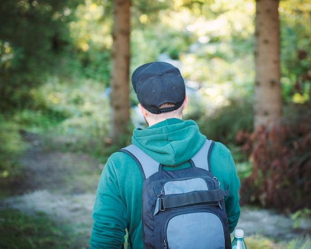 Un homme avec sac à dos se promène dans la forêt d'automne. randonnée seul le long des sentiers forestiers d'automne. notion de voyage.