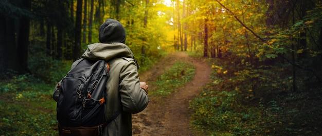 Un homme avec un sac à dos se promène dans l'incroyable forêt d'automne.