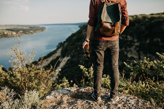 Homme avec sac à dos, tenant des jumelles, debout sur une falaise dans les montagnes.