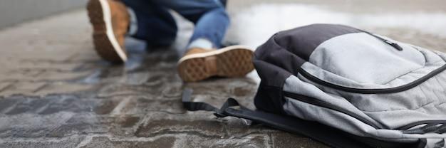Homme avec sac à dos tombant sur un trottoir glissant en hiver libre