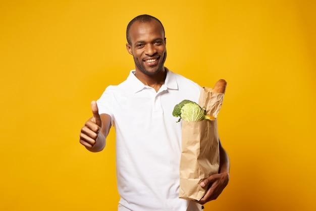 Homme avec sac en papier de produits frais, montrant le pouce vers le haut.