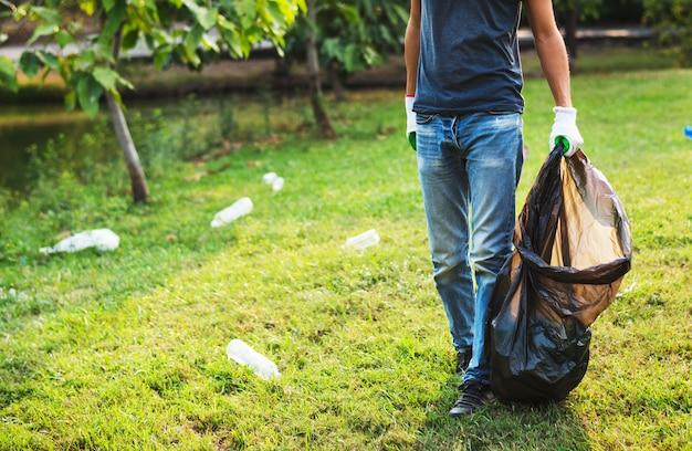 Homme avec un sac en plastique ramasser des bouteilles dans le parc