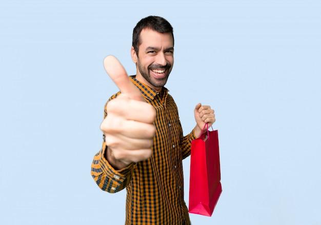 Homme avec des sacs à provisions donnant un geste du pouce levé parce que quelque chose de bon est arrivé sur fond bleu isolé