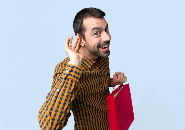 Homme avec des sacs à provisions, écouter quelque chose en mettant la main sur l'oreille sur fond bleu isolé