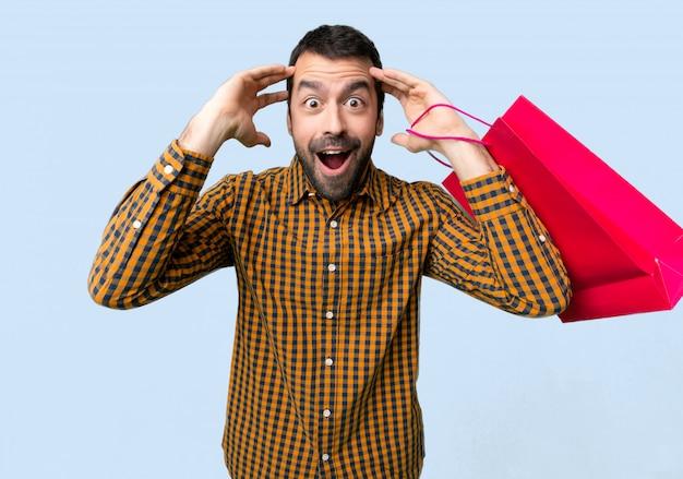 Homme avec des sacs à provisions avec une expression faciale surprise et choquée sur fond bleu isolé