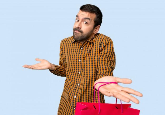 Homme avec des sacs à provisions faisant un geste sans importance tout en soulevant les épaules sur fond bleu isolé