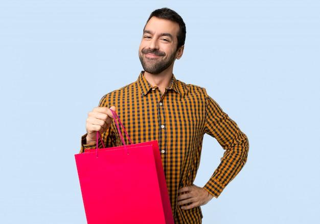 Homme avec des sacs à provisions posant avec les bras à la hanche et souriant sur fond bleu isolé