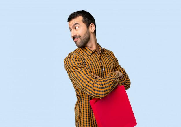 Homme avec des sacs à provisions regardant par-dessus l'épaule avec un sourire sur fond bleu isolé