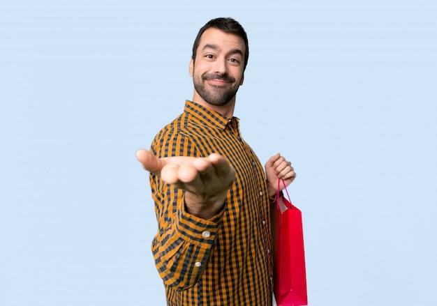 Homme avec des sacs à provisions tenant une surface imaginaire sur la paume pour insérer une annonce sur un fond bleu isolé