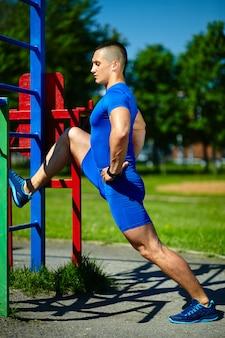 Homme sain athlète srtong heureux beau homme exerçant au parc de la ville - concepts de remise en forme sur une belle journée d'été sur la barre horizontale