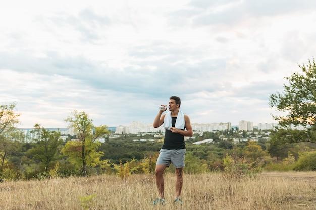 Homme sain, boire de l'eau sur la nature au repos