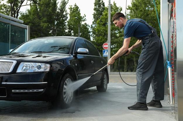 Un homme en salopette lave une voiture dans un lave-auto manuel