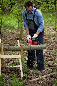 L'homme en salopette scie du bois avec une scie à chaîne à l'aide d'un chevalet en bois