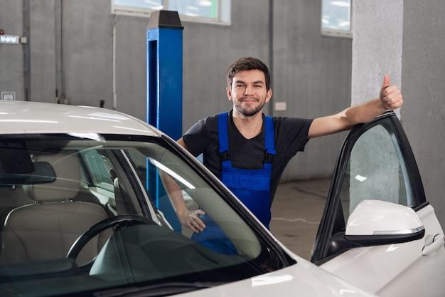 Un homme en salopette se tient à côté d'une voiture blanche