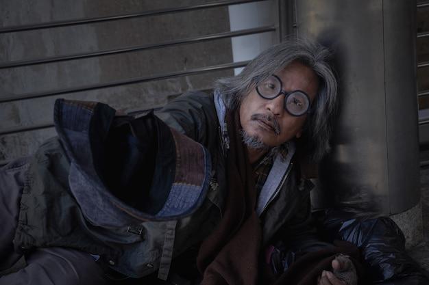 L'homme sans abri est allongé sur un trottoir en ville. il tient un chapeau pour avoir donné de l'argent.