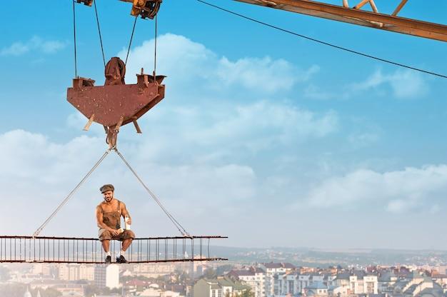 Homme sans peur. beau constructeur hunky joyeux appréciant le déjeuner assis sur une barre transversale suspendue à une grue à la construction