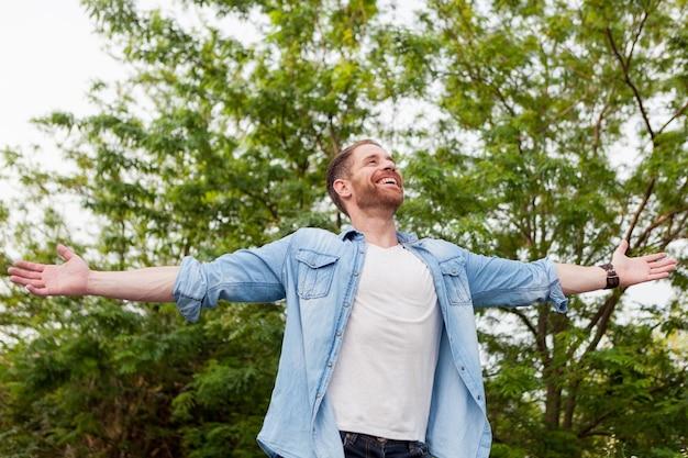 Homme sans soucis et libre levant les bras
