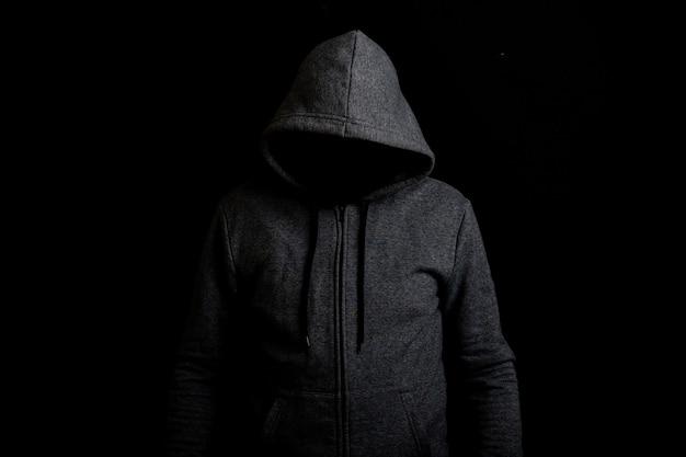 Homme sans visage dans une hotte sur fond sombre.
