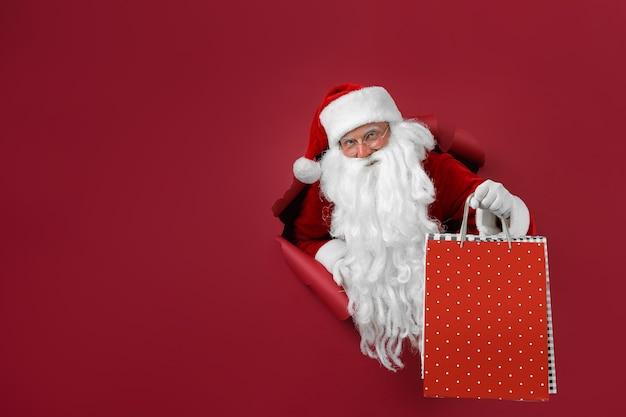 L'homme de santa tient le paquet de magasins dans la main à travers un trou de papier. homme barbu en bonnet de noel regardant à travers le trou sur papier rouge.