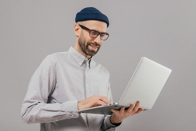 Homme satisfait avec une barbe épaisse et une moustache, tient un ordinateur portable