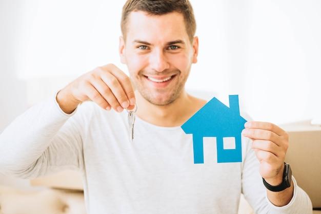 Homme satisfait avec les clés et la maison bleue