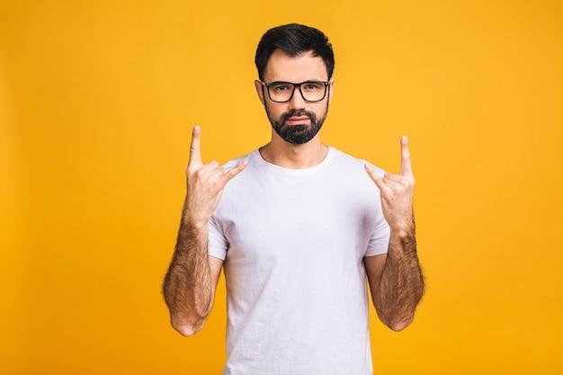 Homme satisfait extrêmement excité à la barbe montrant un geste rock and roll avec les doigts, s'amusant à se reposer sur un concert.