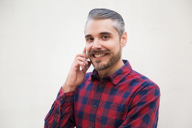Homme satisfait joyeux parler sur cellule