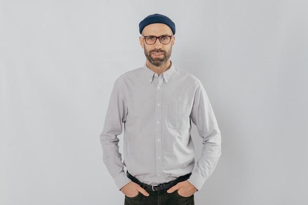 Homme satisfait portant des lunettes à poils, garde les mains dans les poches, habillé de vêtements élégants et classiques