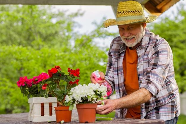 Homme satisfait. retraité barbu portant un chapeau d'été obtenir satisfaction tout en arrosant les plantes
