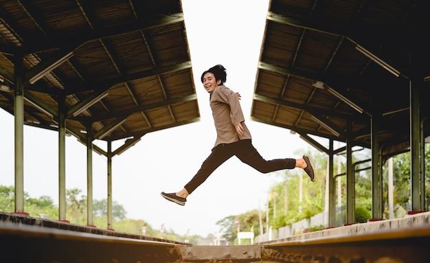 Homme sautant sur le chemin de fer, image pour le concept de voyage et de style de vie