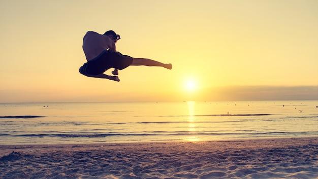 Homme sautant dans un mouvement de taekwondo sur la plage
