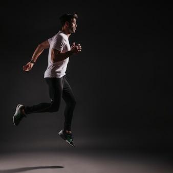 Homme sautant sur fond sombre