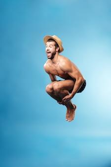 Homme sautant isolé sur mur bleu