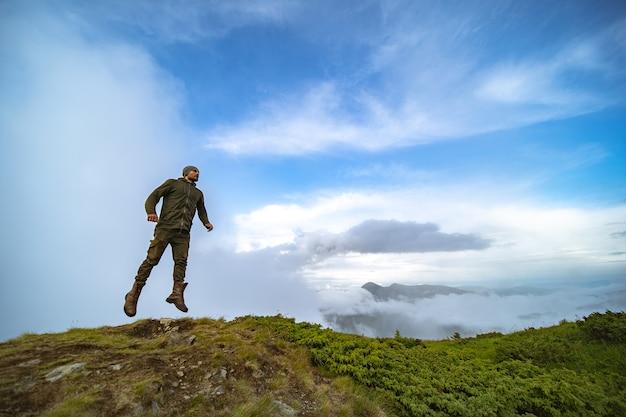 L'homme sautant sur la montagne sur le fond de ciel de nuage