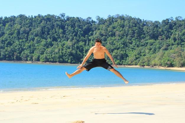 L'homme sautant sur la plage de l'île de phayam