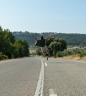 Homme sautant sur la route vide. globe-trotter