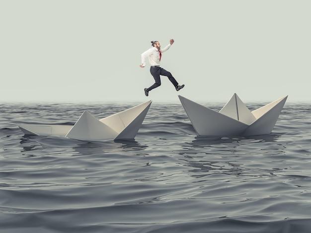 L'homme saute d'un bateau en papier qui coule à un bateau flottant.