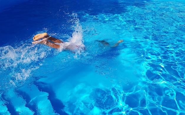 L'homme a sauté dans la piscine bleue