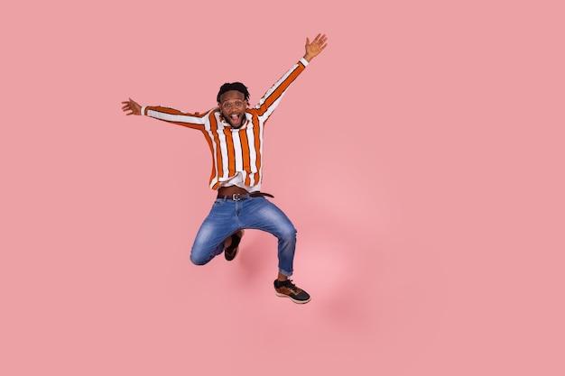 L'homme saute fortement et monte les mains en prétendant qu'il vole en regardant la caméra