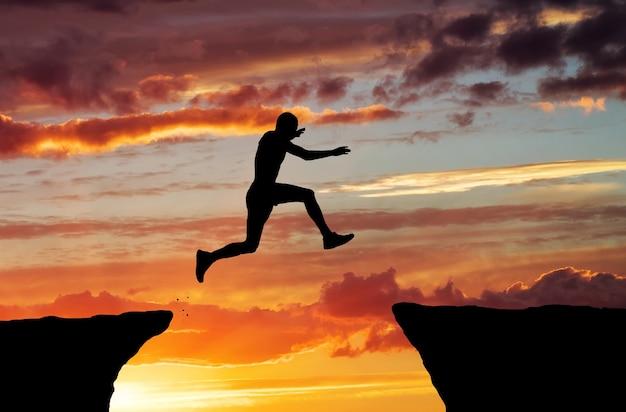 L'homme saute à travers l'écart sur fond de feu de coucher de soleil. élément de conception.