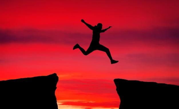 L'homme saute à travers l'écart d'un rocher pour s'accrocher à l'autre. homme sautant par-dessus des rochers avec un écart sur fond de feu de coucher de soleil. élément de conception.
