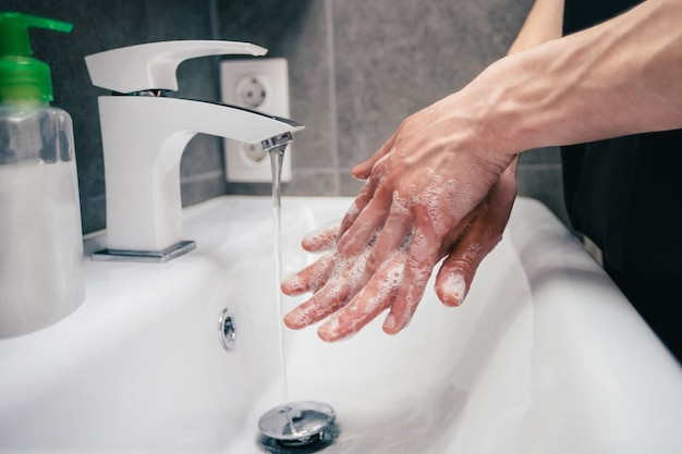 L'homme savonne soigneusement ses mains concept de prévention des maladies infectieuses