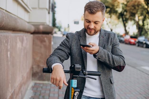Homme scannant le code qr sur un scooter électrique