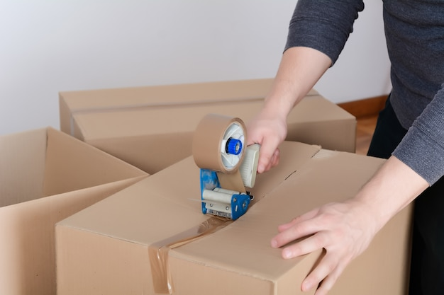 Homme scellant une boîte en carton d'expédition