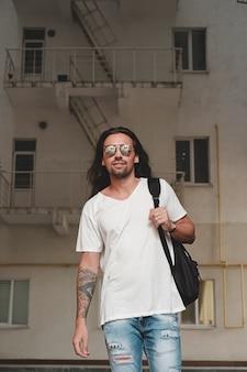 Homme sur scène urbaine avec sac à dos et lunettes de soleil