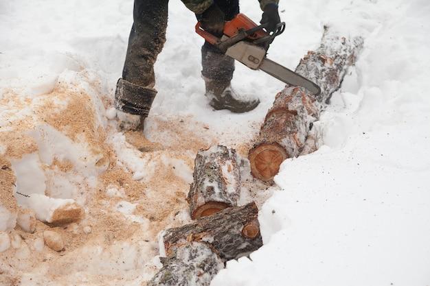 Un homme scie une bûche avec une tronçonneuse dans la neige en hiver