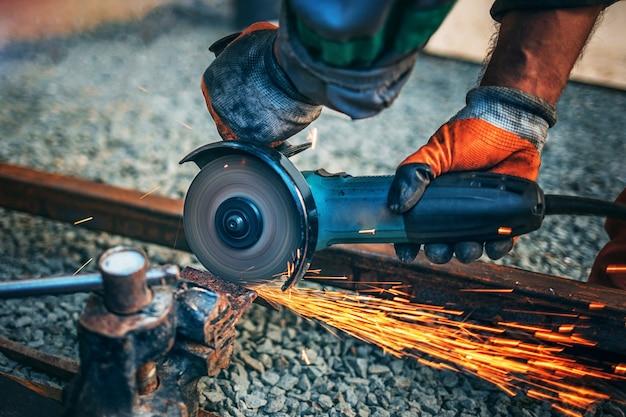 Un homme scie du métal avec une meuleuse d'angle. des étincelles