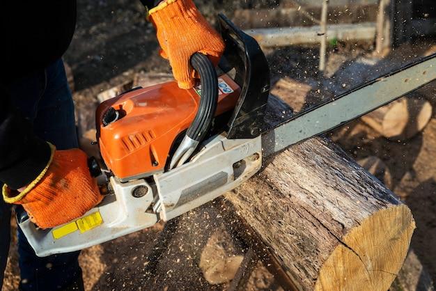L'homme scie une grosse bûche avec une tronçonneuse, gros plan, récolte du bois de chauffage