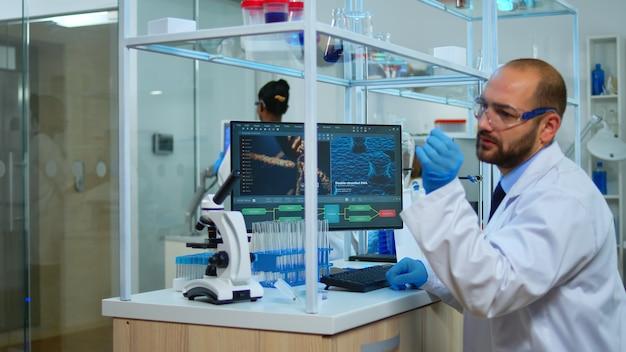 Homme scientifique travaillant au développement de vaccins en tapant sur pc dans un laboratoire moderne. équipe multiethnique examinant l'évolution du virus dans un laboratoire médical à l'aide d'outils chimiques de haute technologie pour la recherche scientifique.